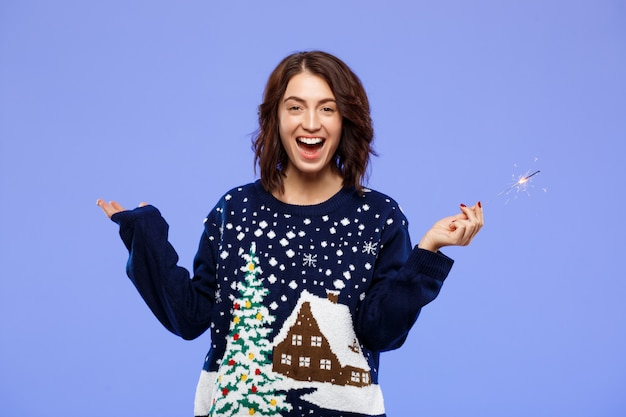 Joven alegre hermosa chica morena en suéter de punto acogedor sonriendo sosteniendo luces de bengala sobre la pared azul