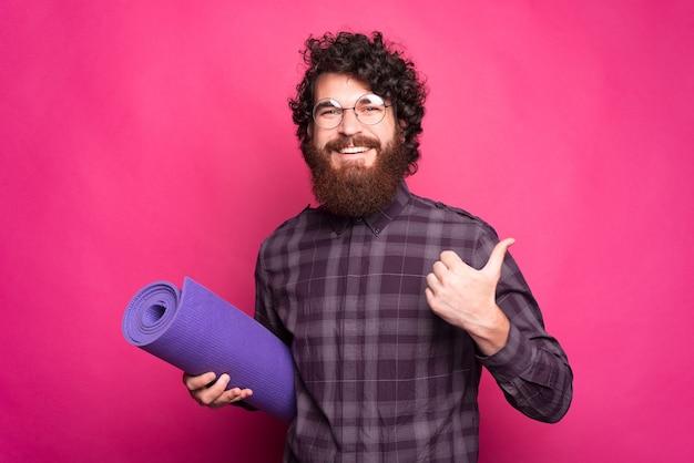 Joven alegre mostrando un pulgar hacia arriba y sosteniendo una estera de yoga