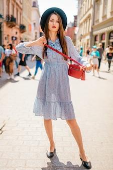 Joven alegre mujer morena en elegante vestido y sombrero posando en la calle de la ciudad con la gente
