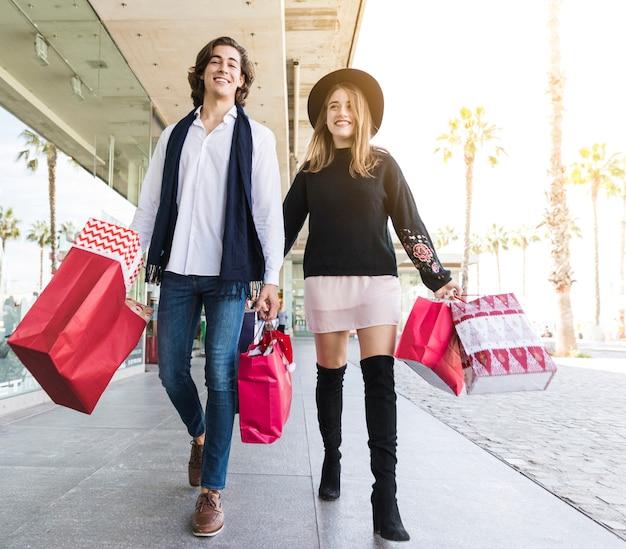 Joven alegre pareja caminando con bolsas de compras