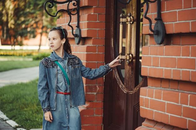 Joven alegre piddle cerca de la puerta del edificio de ladrillo rojo cerca de la hierba verde al aire libre