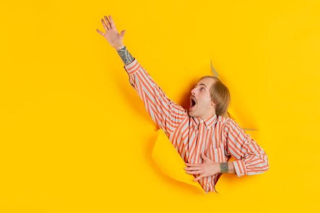 Joven alegre posa en pared de agujero de papel amarillo rasgado emocional y expresivo