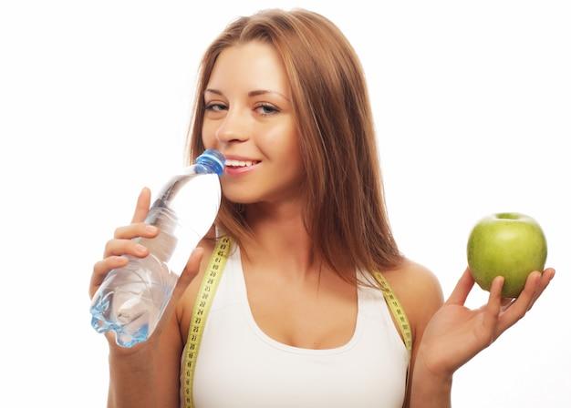 Joven alegre en ropa deportiva con manzana y una botella de agua