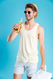 Joven alegre sosteniendo una bolsa más fresca y bebiendo cerveza