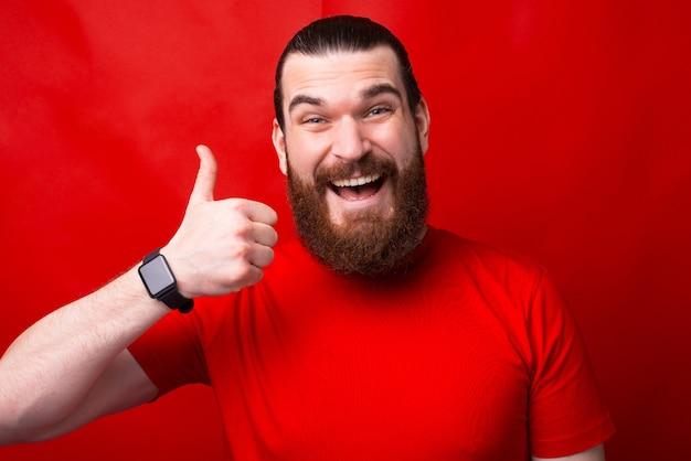 Un joven alegre está sosteniendo un pulgar hacia arriba sonriendo y mirando a la cámara