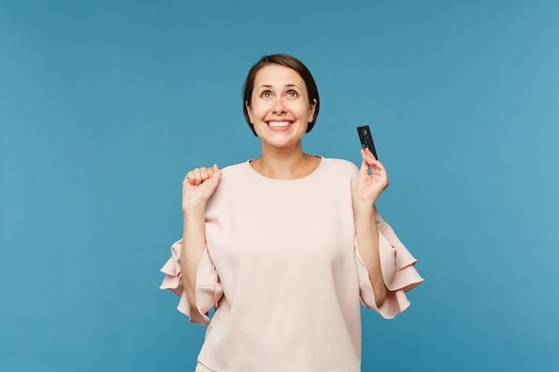 Joven alegre con tarjeta de crédito expresando alegría mientras mira hacia arriba