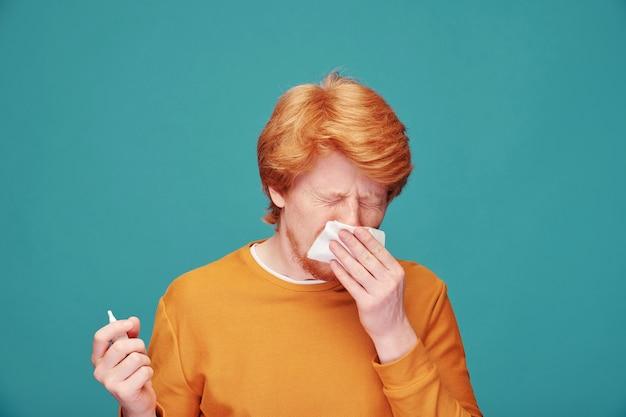 Joven alérgico sosteniendo un pañuelo de papel por la nariz mientras estornuda y usa spray antialérgico frente a la cámara de forma aislada