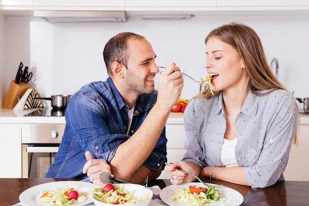 Joven alimentación de ensalada a su esposa sentada en la cocina