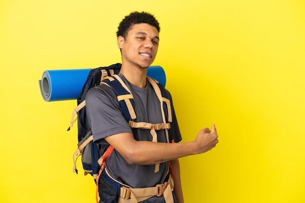 Joven alpinista afroamericano con una gran mochila aislado sobre fondo amarillo apuntando hacia atrás