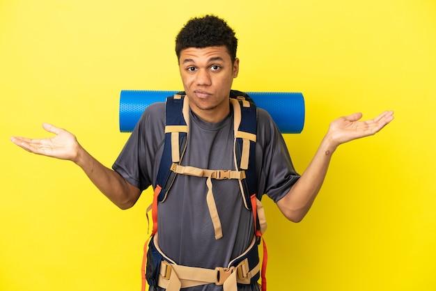 Joven alpinista afroamericano con una gran mochila aislado sobre fondo amarillo con dudas mientras levanta las manos