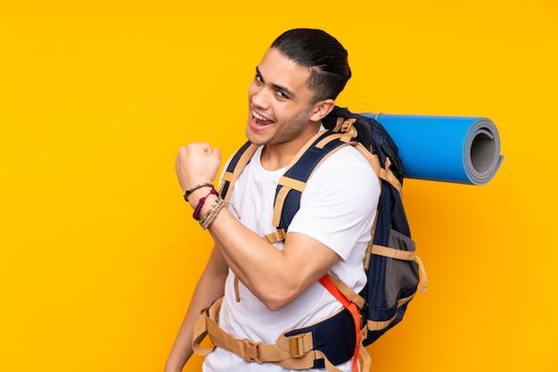 Joven alpinista hombre asiático con una gran mochila en la pared amarilla celebrando una victoria