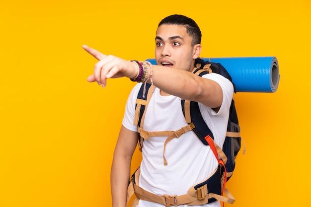 Joven alpinista hombre asiático con una mochila grande en la pared amarilla apuntando lejos