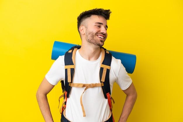 Joven alpinista hombre caucásico con una gran mochila aislada sobre fondo amarillo posando con los brazos en la cadera y sonriendo