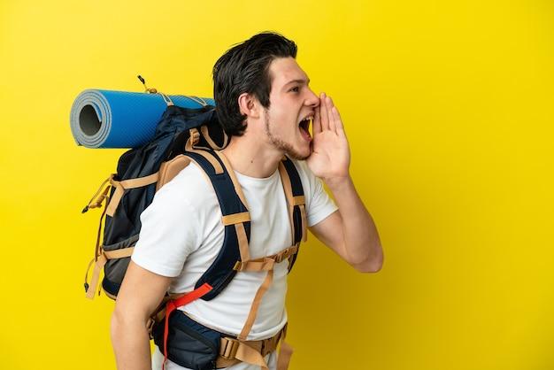 Joven alpinista ruso con una gran mochila aislada sobre fondo amarillo gritando con la boca abierta hacia el lado
