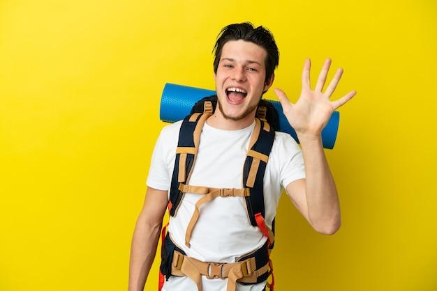 Joven alpinista ruso con una gran mochila aislado sobre fondo amarillo contando cinco con los dedos