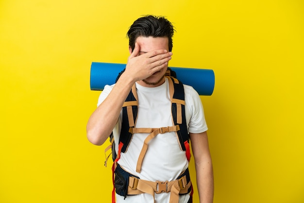 Joven alpinista ruso con una mochila grande aislada sobre fondo amarillo que cubre los ojos con las manos. no quiero ver algo