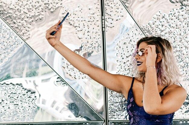 Una joven alternativa usando su teléfono móvil con vestido violeta y labios