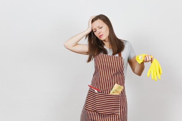 Joven ama de casa cansada molesta triste en delantal de rayas con trapo de limpieza en el bolsillo aislado