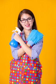 Joven ama de casa femenina con productos de limpieza