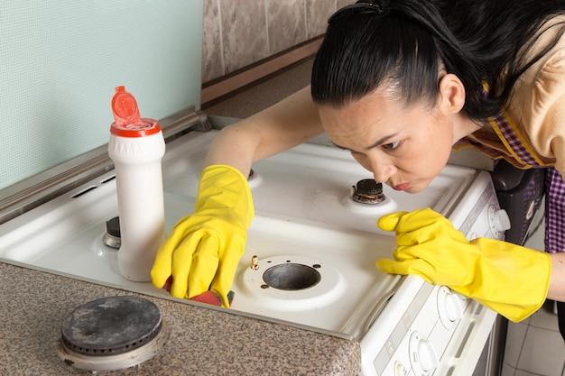 Joven ama de casa con guantes amarillos de limpieza de la estufa de gas