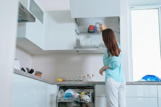 Joven ama de casa pone platos limpios del lavavajillas en los estantes del gabinete de la cocina, vista posterior