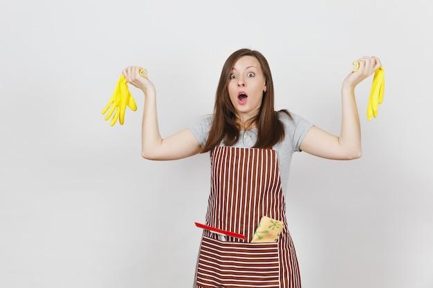 Joven ama de casa sorprendida cansada trastornada triste en delantal rayado con el trapo de limpieza en el bolsillo aislado. mujer bonita ama de llaves sosteniendo guantes amarillos en manos extendidas