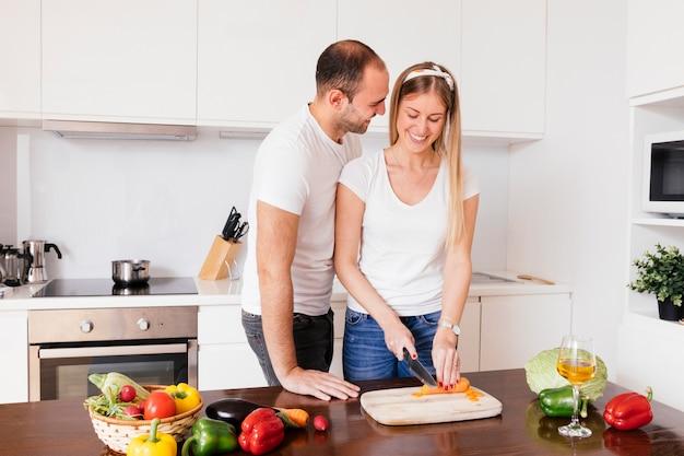 Joven amante de su novia cortando la zanahoria con un cuchillo
