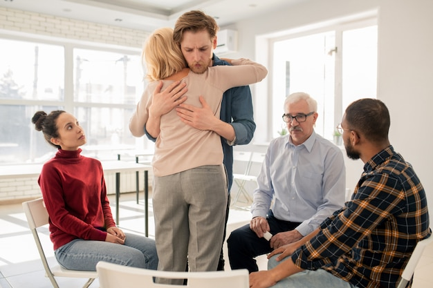 Joven amigable apoyando a la mujer rubia madura mientras le da un abrazo en la sesión de terapia psicológica