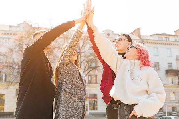 Joven amigo levantando las manos apiladas juntos