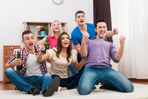Joven amigo viendo la televisión y animando el fútbol
