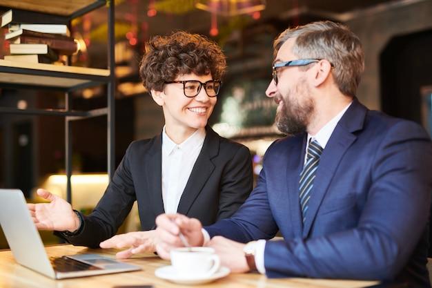 Joven analista o corredor exitoso que muestra los datos en línea de su colega mientras discute los cambios en la tasa financiera