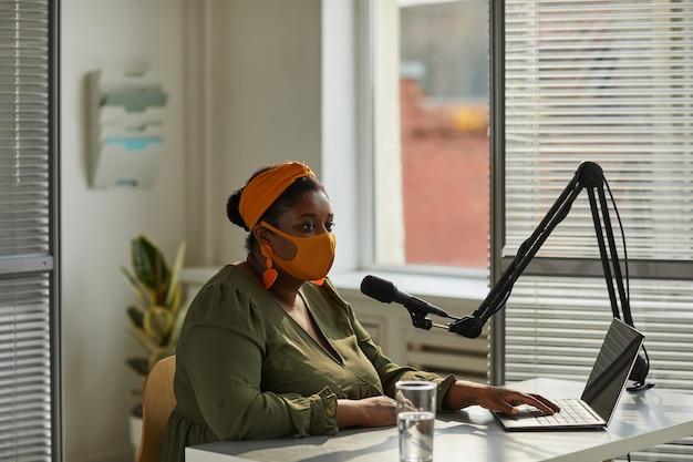 Joven anfitrión en máscara hablando por micrófono trabajando en radio durante la pandemia
