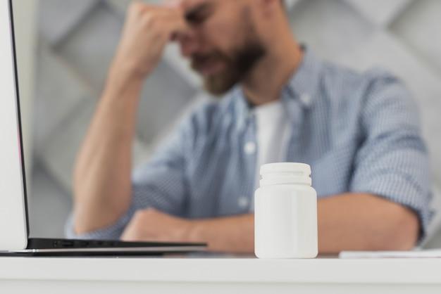 Joven de ángulo bajo en la oficina con dolor de cabeza