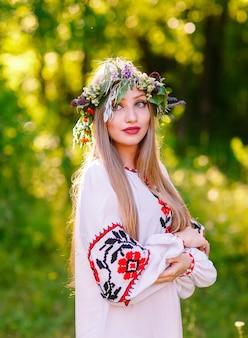 Una joven de apariencia eslava con una corona de flores silvestres en el verano.