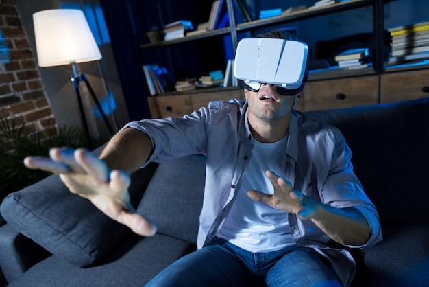Joven apasionado pasando una noche en casa y probando su nueva compra mientras usa equipo de realidad virtual