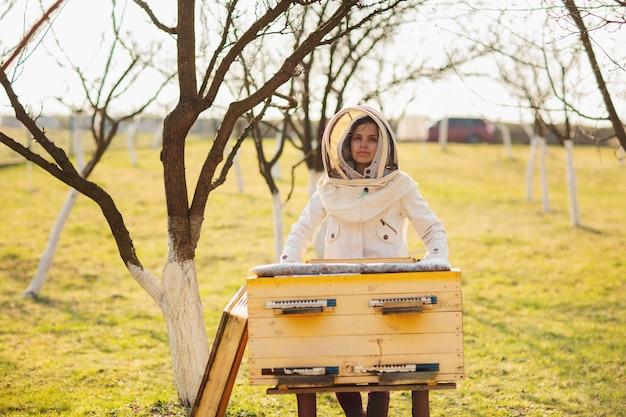 Una joven apicultora está trabajando con abejas y colmenas en el colmenar.