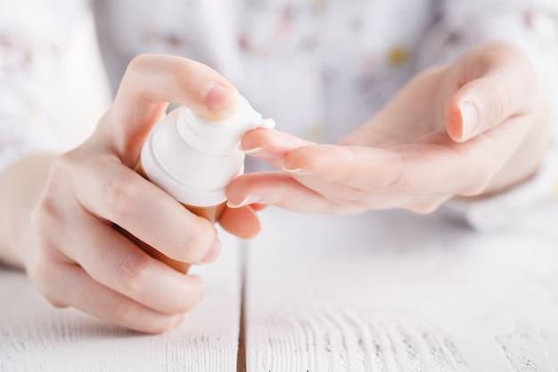 Joven aplica crema en sus manos.