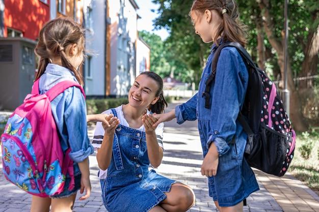 Una joven apoya moralmente a las hijas cogidas de la mano, anima a los niños, acompaña a los alumnos a la escuela.
