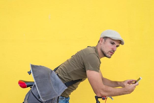 Joven, apoyado en bicicleta, utilizando teléfonos inteligentes