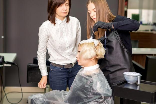 Joven aprendiz aprende a dibujar el cabello de las mujeres bajo la supervisión de un peluquero profesional en una barbería