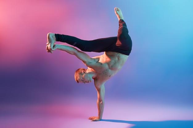 Joven apuesto acróbata o gimnasta entrenando para mantener el equilibrio de su cuerpo, de pie sobre una mano mientras está descalzo y en topless, tocando su pierna, mostrando su poder.