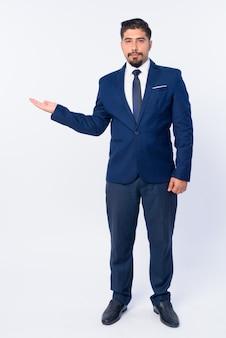 Joven apuesto empresario iraní barbudo en traje aislado en blanco