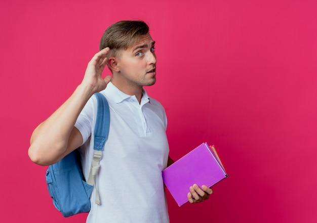 Joven apuesto estudiante masculino con mochila sosteniendo libros y mostrando gesto de escuchar