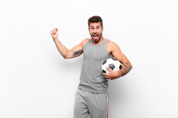 Joven apuesto gritando triunfante, luciendo emocionado, feliz y sorprendido ganador, celebrando sosteniendo un balón de fútbol