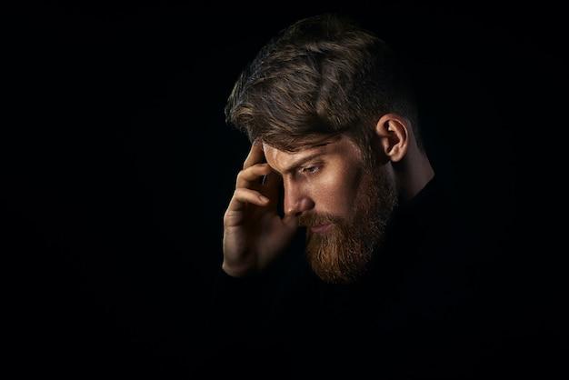 Joven apuesto hombre barbudo con barba y elegante corte de pelo piensa