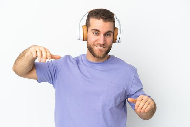 Joven apuesto hombre caucásico aislado en la pared blanca escuchando música y bailando