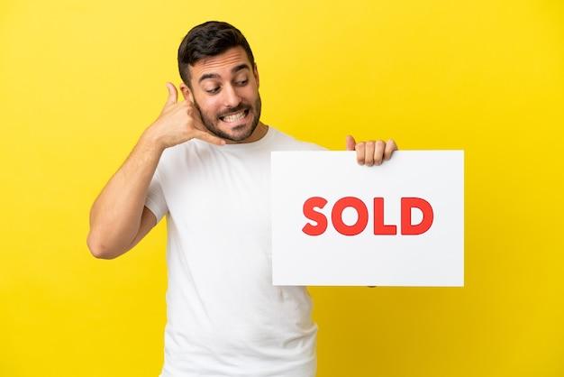 Joven apuesto hombre caucásico aislado sobre fondo amarillo sosteniendo una pancarta con el texto vendido y haciendo el gesto que viene