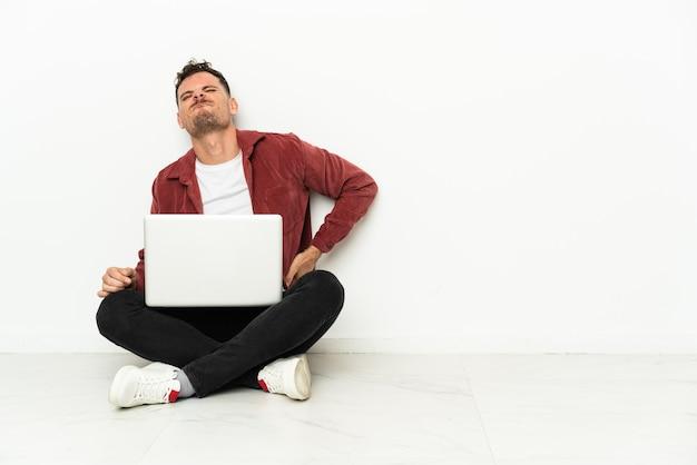 Joven apuesto hombre caucásico sentado en el suelo con un portátil que sufre de dolor de espalda por haber hecho un esfuerzo
