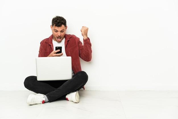 Joven apuesto hombre caucásico sentado en el suelo con portátil sorprendido y enviando un mensaje