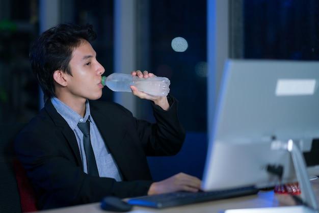 Joven apuesto hombre de negocios asiático bebiendo agua después de trabajar duro en la oficina por la noche
